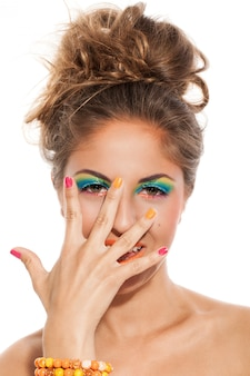 Menina com manicure colorido e maquiagem