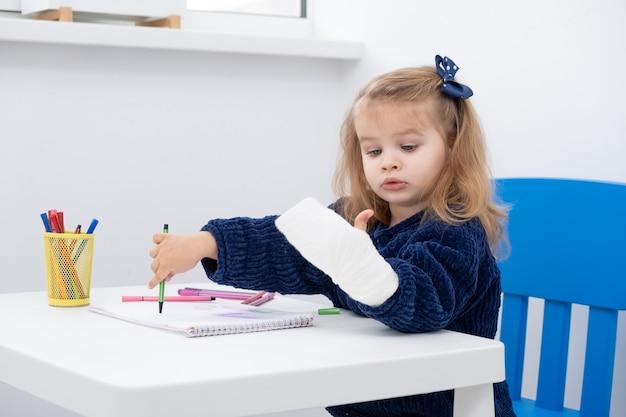 Menina com mão no gesso, sentado à mesa tentando desenhar com marcadores.