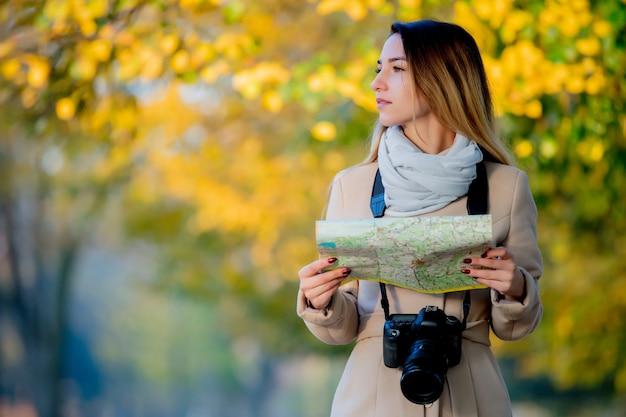 Menina com mapa e câmera, procurando o caminho na rua.