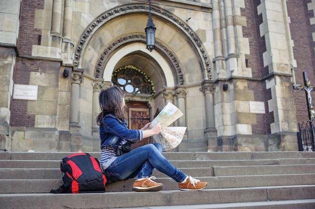Menina com mapa sentado na escada e olha para a igreja velha