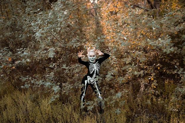 Menina com maquiagem assustadora, vestida como um esqueleto. dia das bruxas, conceito de férias de outono