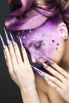 Menina com maquiagem criativa roxa brilhante com cristais e unhas compridas. rosto bonito. foto tirada no estúdio em um fundo cinza.