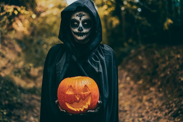 Menina com maquiagem de halloween, segurando uma abóbora na madeira