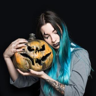 Menina com maquiagem de palhaço segurando abóbora assustadora