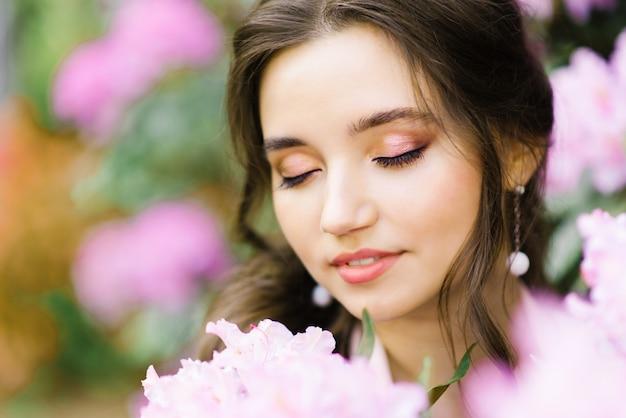Menina com maquiagem profissional, mais o tamanho em um jardim florescendo fechou os olhos