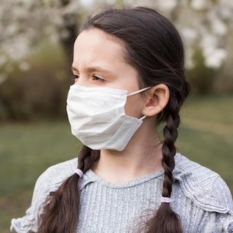 Menina com máscara ao ar livre