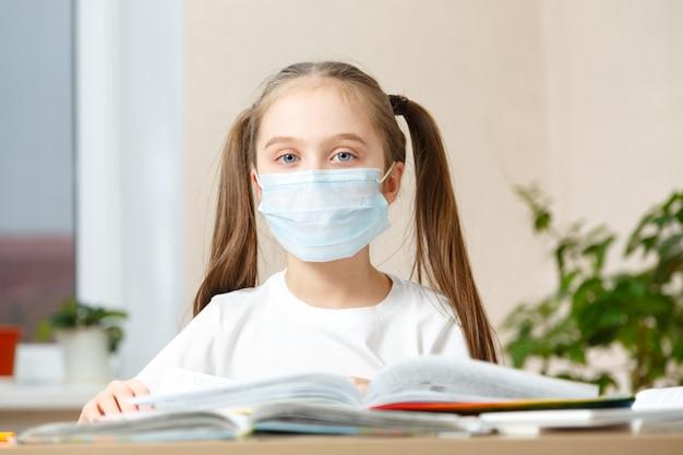 Menina com máscara de proteção no ensino doméstico à distância, quarentena