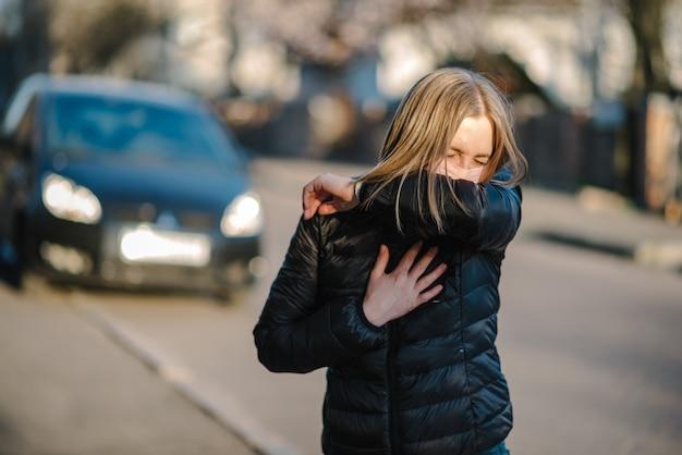 Menina com máscara durante a pandemia de covid-19, tossindo na rua. os perigos do coronavírus. risco de propagação de infecção. cobrindo o nariz e a boca, espirrando o cotovelo flexionado. mulher tosse na prevenção do braço.