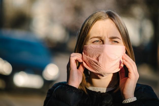 Menina com máscara durante a pandemia de covid-19, tossindo ou espirrando na rua. os perigos do coronavírus. risco de propagação de infecção. cobrindo o nariz e a boca. mulher tosse na prevenção do braço.