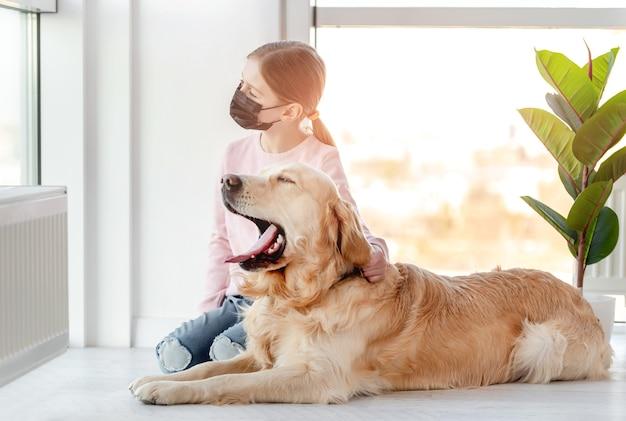 Menina com máscara e cachorro golden retriever