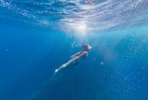 Menina com máscara e snorkel mergulha no mar com corais e peixes