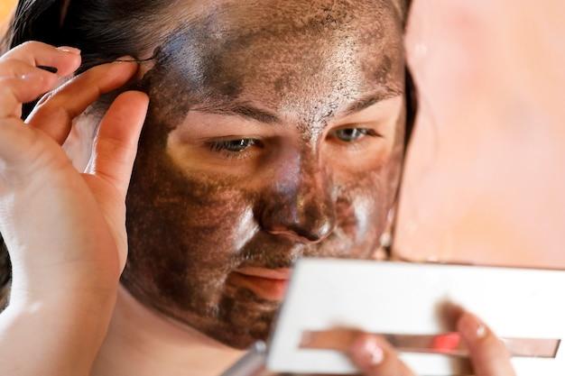 Menina com máscara facial de lama terapêutica. procedimento cosmético para o rosto. rejuvenescimento da pele. foto de alta qualidade