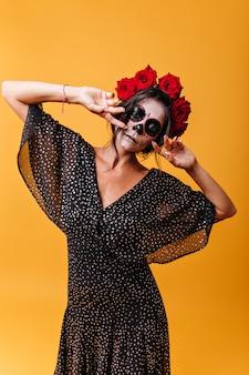 Menina com máscara facial de mexicano étnico posando com olhar misterioso na parede isolada. retrato de uma mulher incomum com rosas no cabelo
