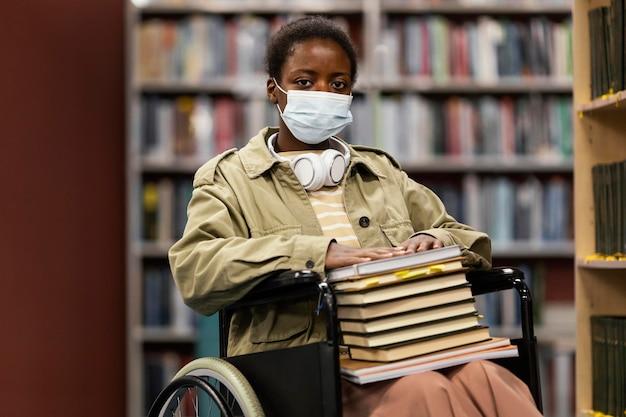 Menina com máscara facial em cadeira de rodas segurando um monte de livros
