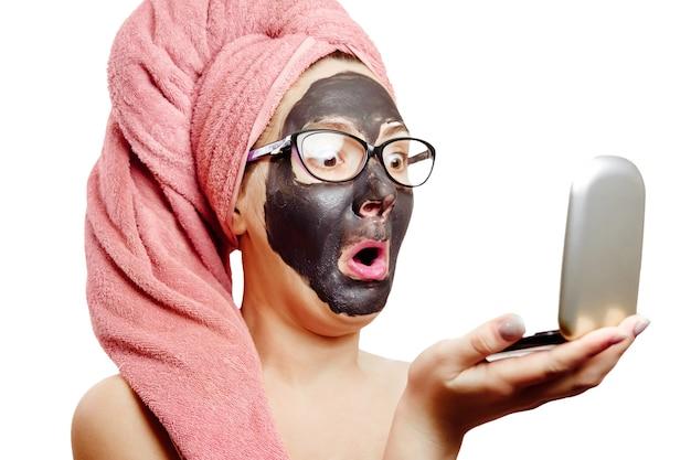 Menina com máscara facial preta em fundo branco, retrato em close-up, isolado, toalha rosa na cabeça, mulher de negócios de óculos, menina olha horrorizada para si mesma no espelho pequeno