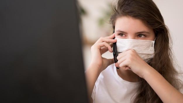 Menina com máscara falando por telefone