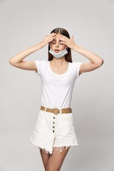 Menina com máscara médica e com os olhos fechados toca a cabeça com as mãos, shortinho de problemas de saúde e camiseta
