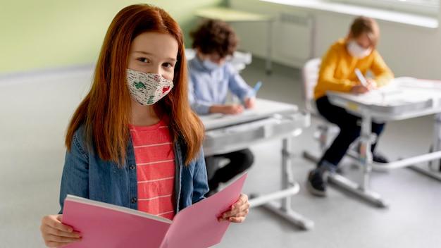 Menina com máscara médica e livro em sala de aula