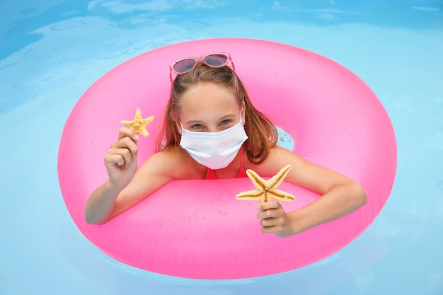 Menina com máscara médica na cara na piscina.