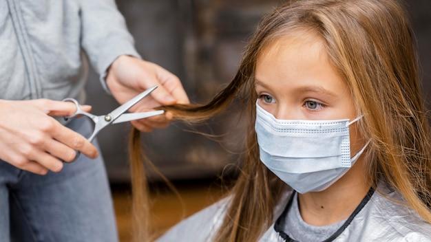 Menina com máscara médica no cabeleireiro