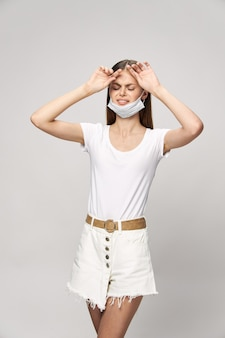 Menina com máscara médica, olhos fechados, dor de cabeça, segurança, saúde, proteção