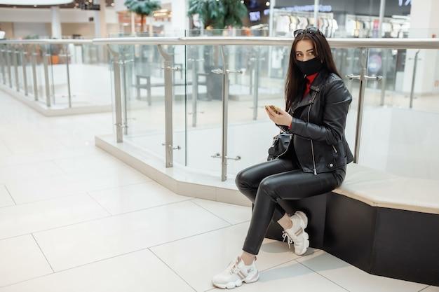 Menina com máscara médica preta e telefone celular em um shopping center