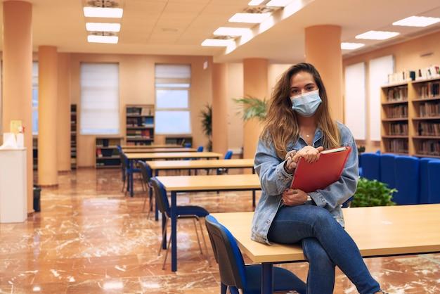 Menina com máscara olha para a câmera com uma biblioteca vazia ao fundo