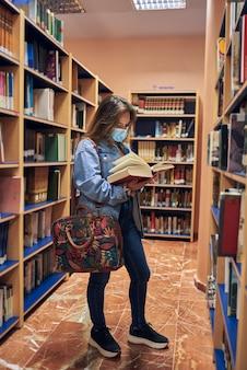 Menina com máscara olhando para um livro entre as estantes de uma biblioteca