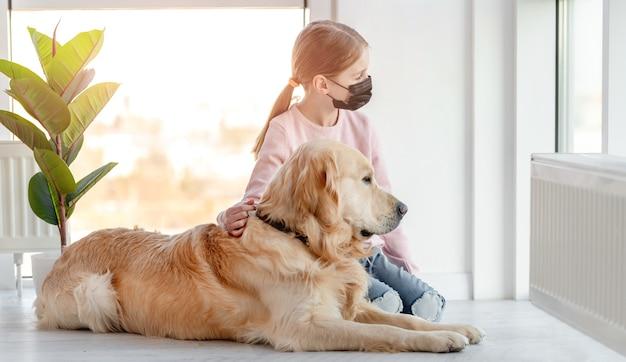 Menina com máscara preta e cachorro golden retriever sentados juntos no chão e olhando pela janela