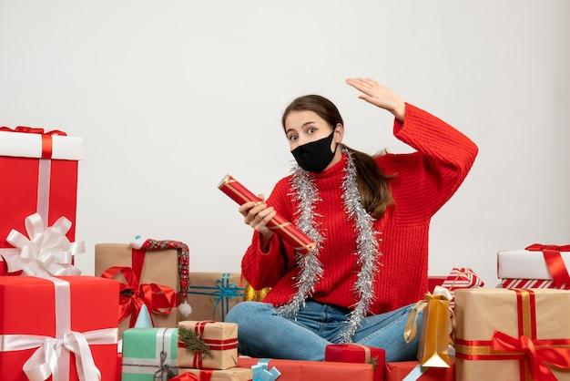 Menina com máscara preta segurando um popper de festa sentada em volta de presentes em branco