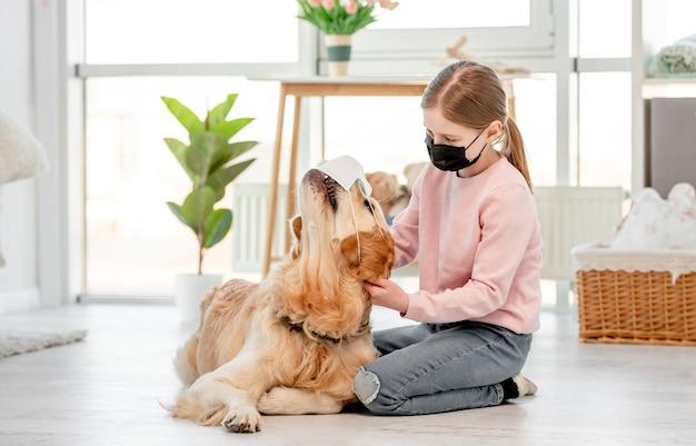 Menina com máscara preta sentada no chão em um quarto ensolarado e acariciando o cachorro golden retriever