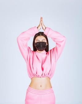 Menina com máscara preta, unindo as mãos e orando.
