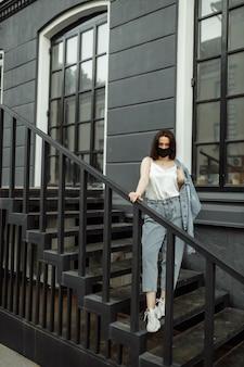 Menina com máscara protetora em uma varanda olha para uma cidade vazia
