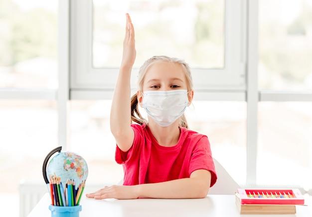 Menina com máscara protetora levantando a mão sentada na mesa da escola