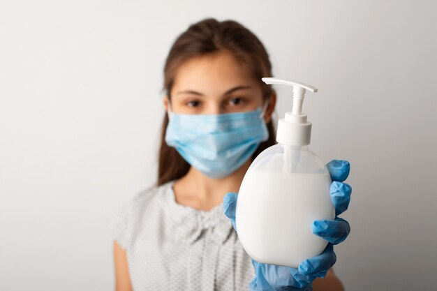 Menina com máscara protetora médica mostrando frasco com sabonete