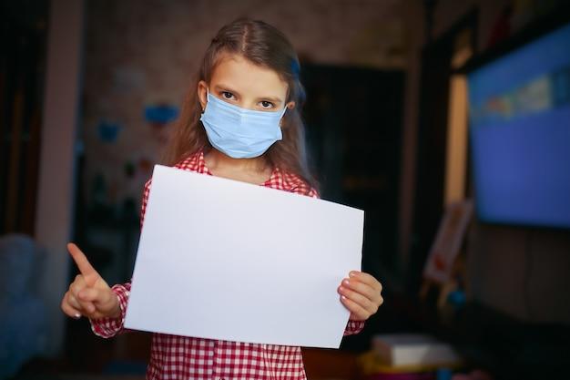 Menina com máscara protetora, pijama segura uma folha de papel em branco com uma das mãos e a outra aponta o dedo enquanto está na sala de casa. proteção contra coronavírus
