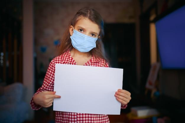 Menina com máscara protetora, pijama segura uma folha de papel em branco com uma das mãos e a outra aponta para a folha enquanto está na sala de casa. proteção contra coronavírus