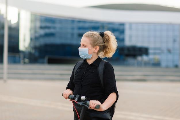 Menina com máscara saindo de casa para ir para a escola em uma scooter
