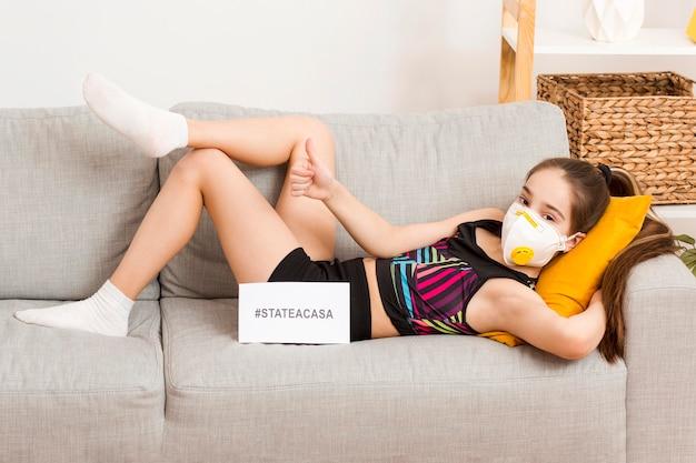 Menina com máscara sentada no sofá
