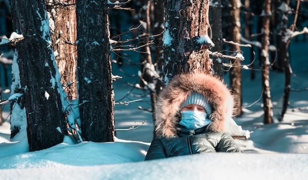 Menina com máscara sob a árvore com os olhos fechados na floresta de inverno.