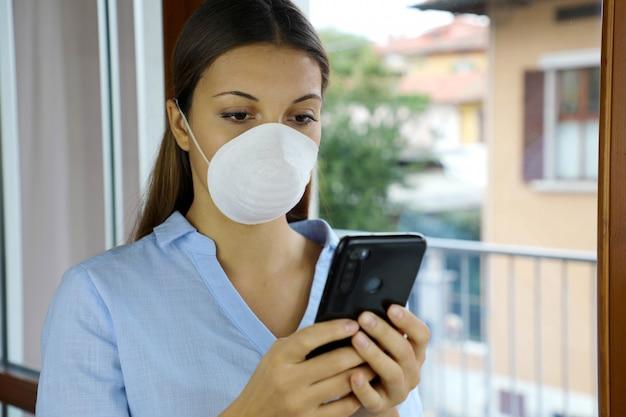 Menina com máscara usando telefone celular em casa.