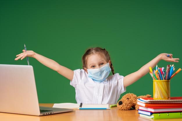 Menina com máscara usando um laptop para estudar
