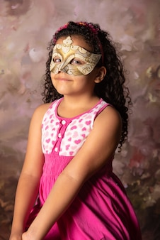 Menina com máscara veneziana e vestido rosa