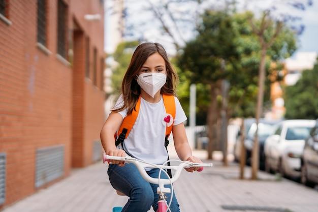 Menina com máscaras andando de bicicleta na rua durante a pandemia de coronavírus.