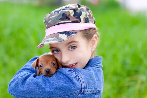 Menina com mascote de cachorrinho de estimação mini pinscher