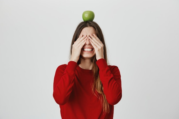 Menina com medo de olhar como segurando o alvo de maçã na cabeça e esperando o tiro de flecha