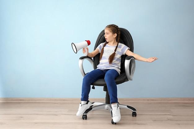 Menina com megafone sentada na cadeira em um quarto vazio