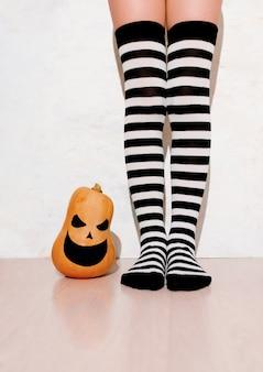 Menina com meias listradas ao lado de uma abóbora de halloween