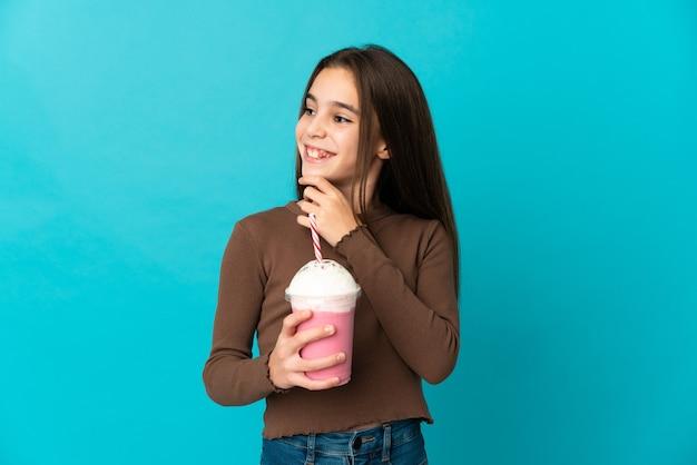 Menina com milk-shake de morango isolada em um fundo azul olhando para o lado e sorrindo