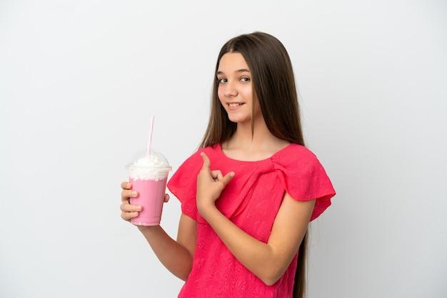 Menina com milk-shake de morango sobre fundo branco isolado apontando para trás